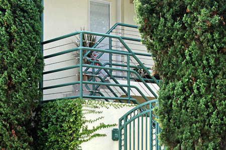 Shrubery and metal gate and stairwell at Cedar Street Apartments