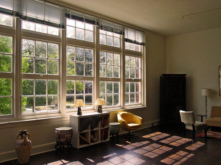 Large windows with sunlight shining onto hardwood floors