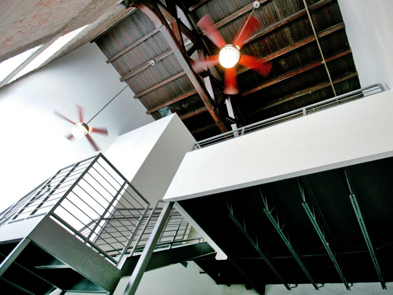 fans spinning in heigh ceiling lofts apartment with metal staircase