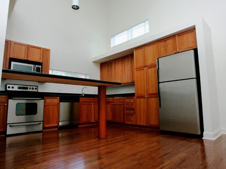 Kitchen with hardwood floors, wood cabinetry and stainless steel applicance